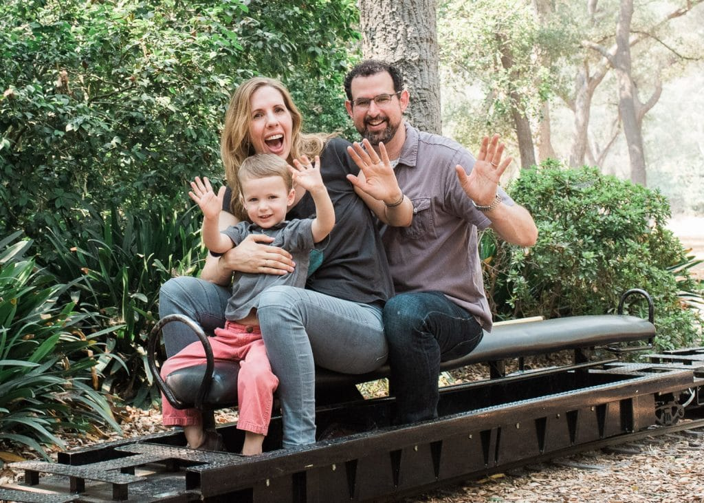 family waving from train