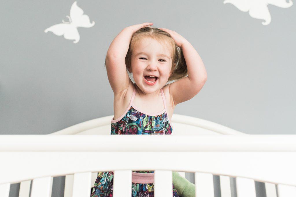 toddler-girl-laughing-in-crib