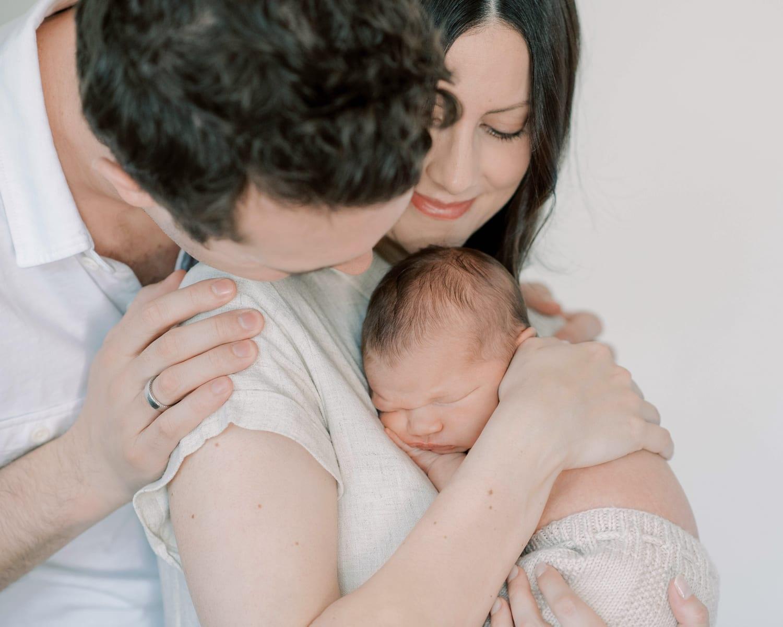 mom and dad cuddling newborn son