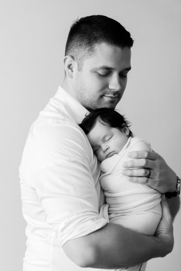 Black and white portrait of father cuddling newborn daughter