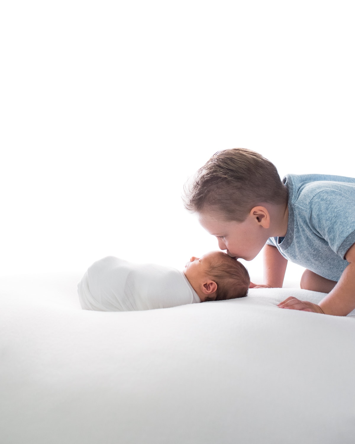 big brother kissing swaddled newborn's head