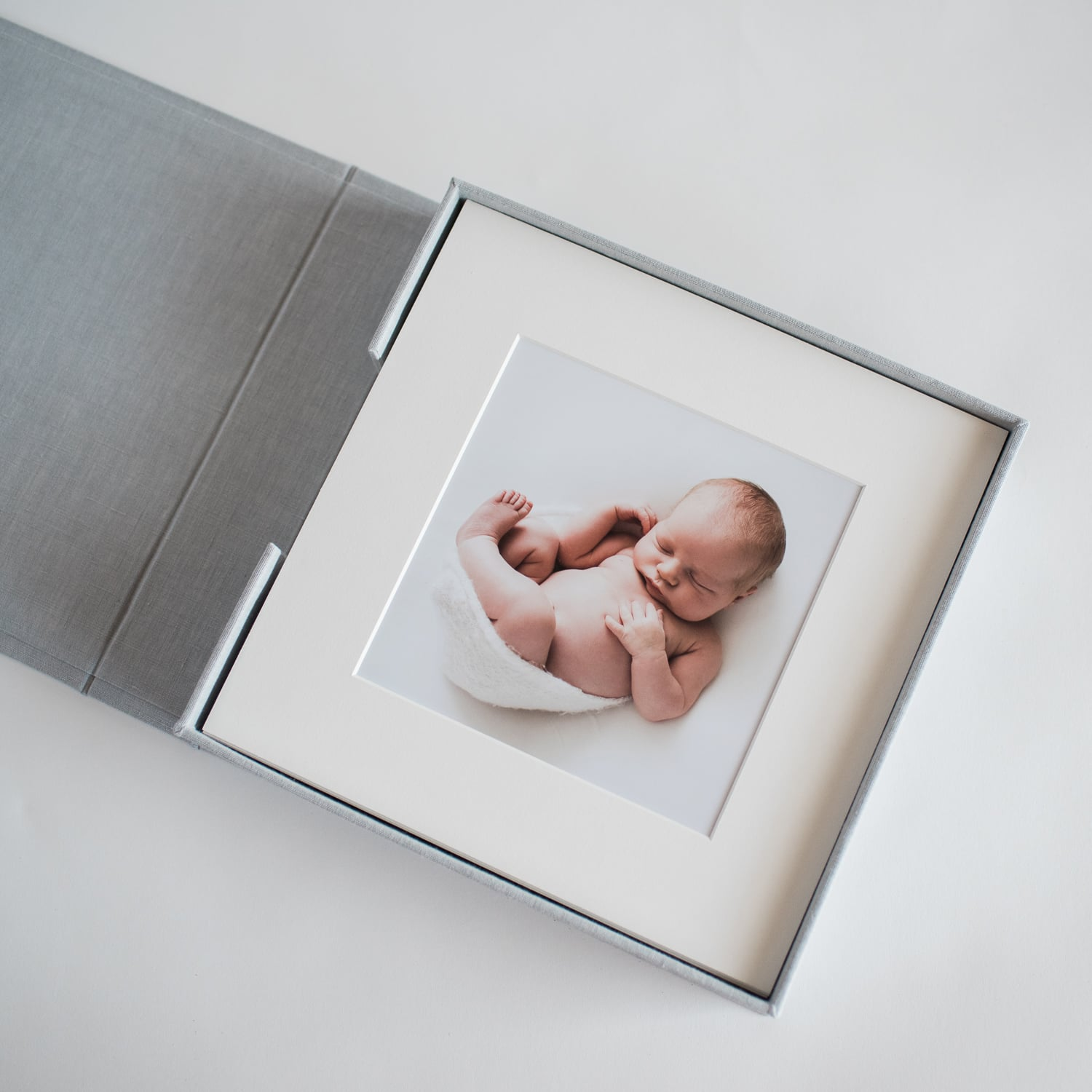 Overhead shot of box of matted newborn portraits
