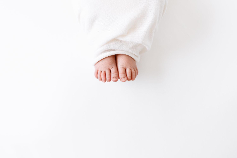 newborn feet peeking out of blanket
