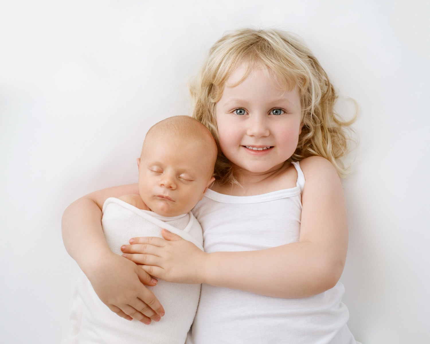 baby sister holding newborn brother