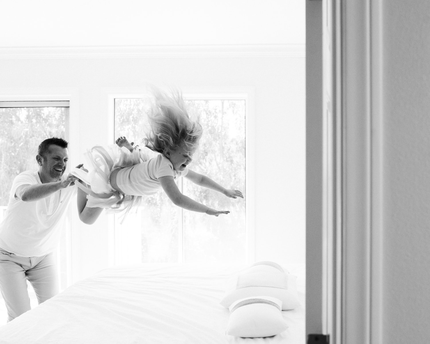 black and white image of father tossing his child onto the bed