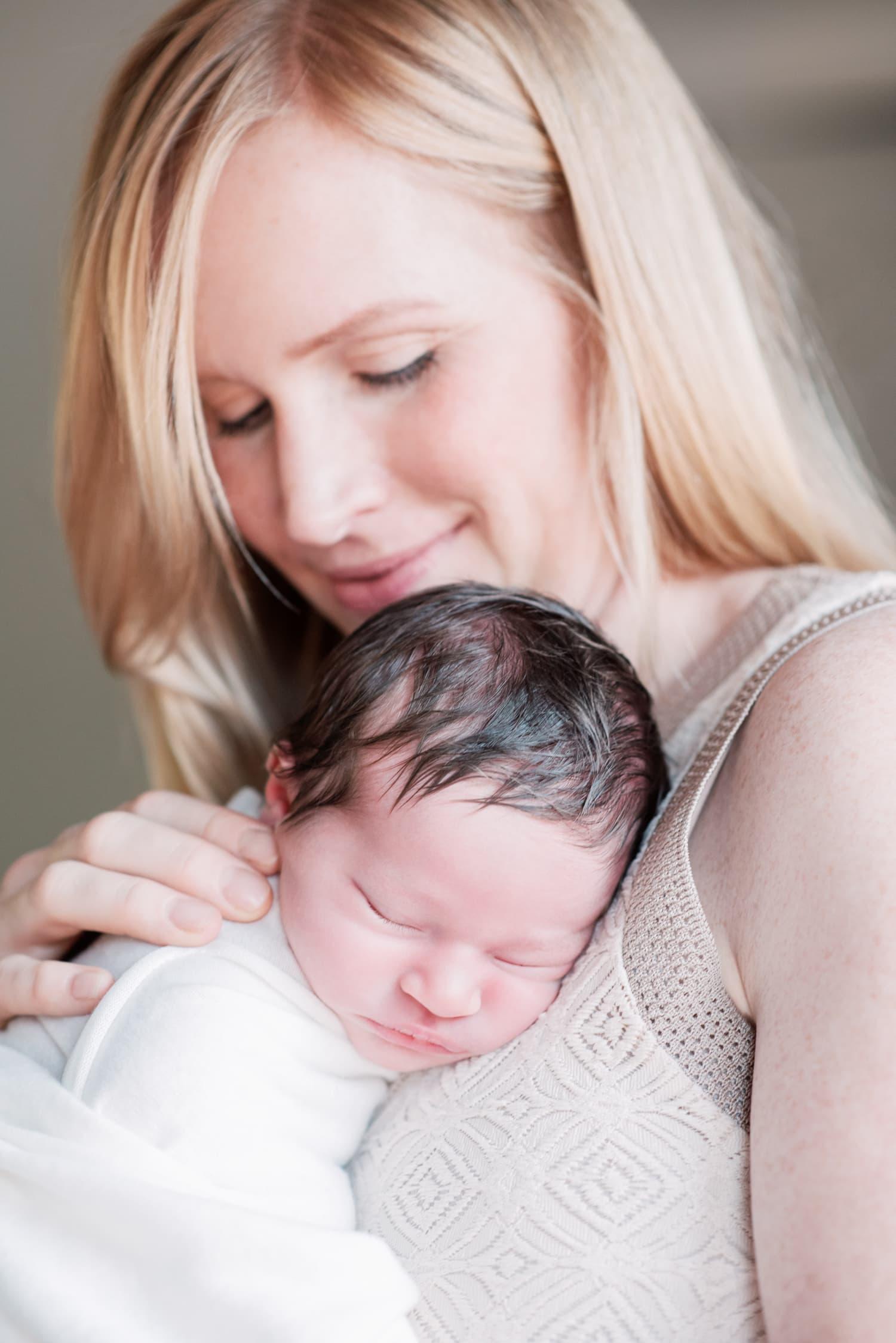 portrait of mom cuddling newborn daughter