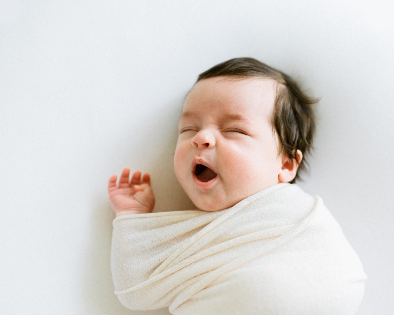 Overhead portrait of swaddled newborn yawning