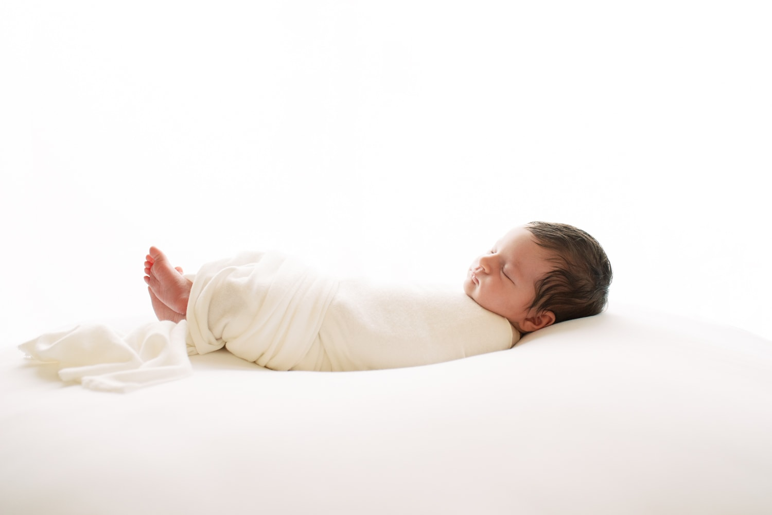 photograph of swaddled newborn in profile